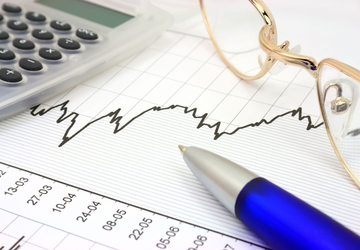 A photo of a stock graph or chat needed for license or permit bonds with a pair of glasses and pen.